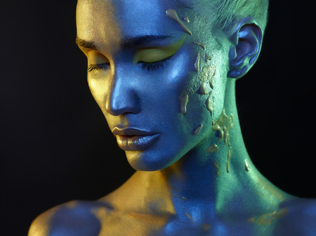 Body art. conceptual make-up. silver skin beauty girl.close-up fashion portrait of woman face in colored spotlights Standard-Bild