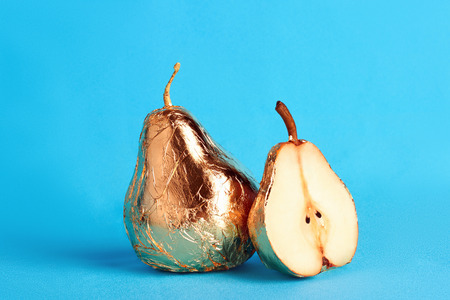 vitamines: pear in gold foil.fruit beauty still life Stock Photo