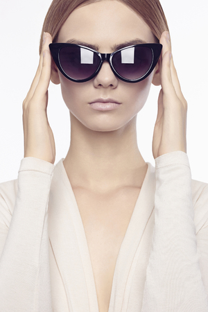 seductress: beautiful young woman with make-up.fashion beauty girl in glasses. trendy sunglasses Stock Photo