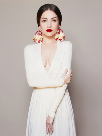 Elegant fashion photo of glamor beautiful young woman in sexy dress posing in the studio,luxury.beauty brunette girl with red lips and accessories