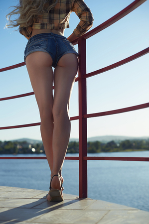 booty: Beautiful body girl on a lighthouse.young summer woman jeans shorts booty