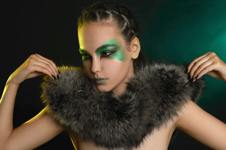 fantasy woman in fur and green make-up.fairy beautiful girl.barbarian who lives in the woods Stock Photo