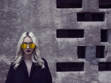 Portrait of fashionable blonde girl wearing a black top coat and colorful glasses.young woman walking in city