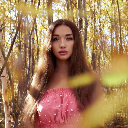 lifestyle Outdoor fashion photo of young beautiful woman surrounded autumn leaves.beauty girl walking in forest