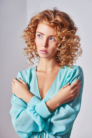 Blonde girl with healthy wavy hair. Beautiful model with curly hairstyle