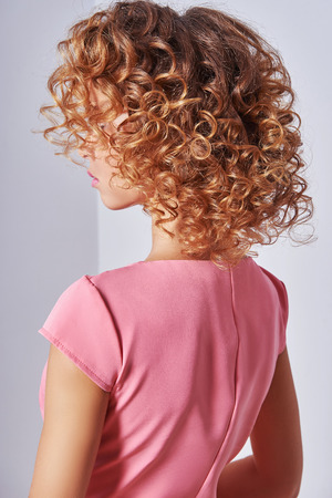 Beauty girl with blonde curly hair. Healthy Blond Wavy hair.Beautiful young woman. Backside. Hair perm, Hair extensions Stock Photo