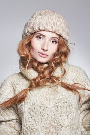 fashion portrait of winter style beautiful young Woman in fashionable woolen hat and pullover.Girl in warm sweater Stock Photo