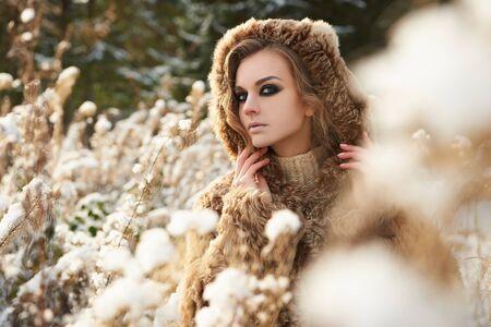 visone: Moda, bellezza ritratto all'aperto di giovane donna in cappuccio di pelliccia. bella ragazza modello nella neve forest.wild inverno natura Archivio Fotografico