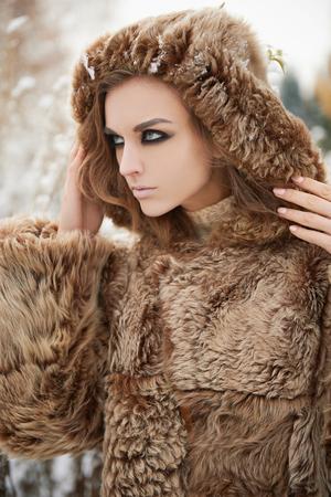 visone: primo piano moda bellezza all'aperto ritratto di giovane donna in cappuccio di pelliccia. bella ragazza modello nella neve forest.wild inverno natura