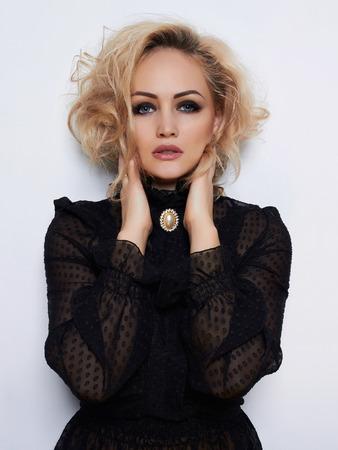 巻き毛のヘアスタイルと美しさブロンドの女の子。美しい情熱のモデルの少女