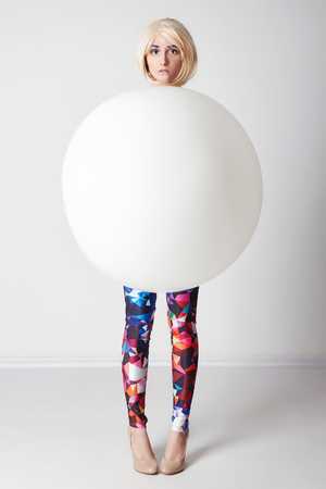 funny girl in a ball.fashion art photo of young woman in big balloon