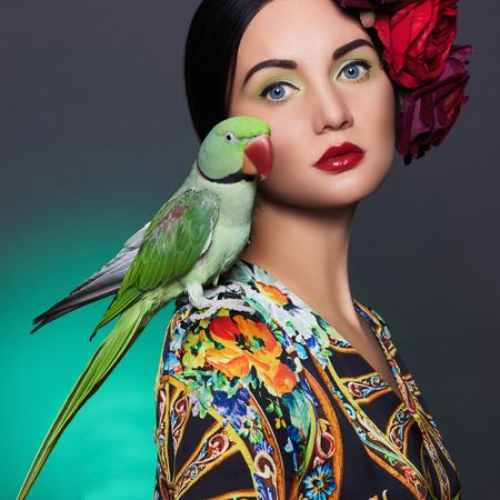 mooi meisje met een papegaai en een bloem in haar haar. Schoonheid jonge vrouw met kleurrijke make-up en vogel