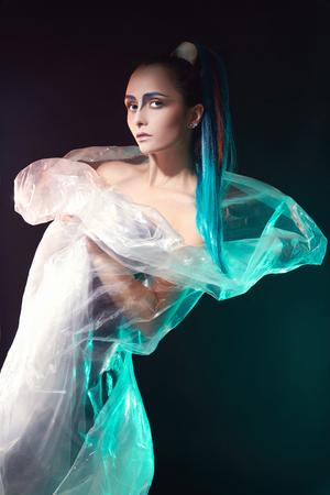 青い髪と彼女の顔にペイントの plastic.young 女性の未来的なメイクの女の子