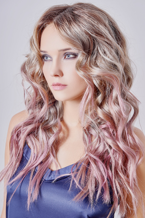 Beautiful girl with long wavy hair. fair-haired model with curly hairstyle and fashionable makeup