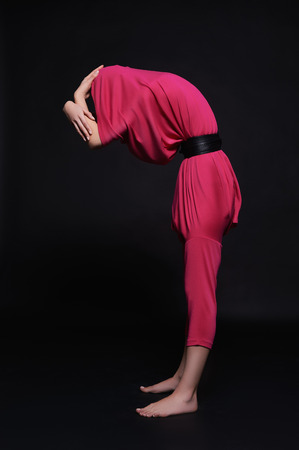 Girl hides her face in unusual clothes and strange pose.abstract fashion art Banco de Imagens