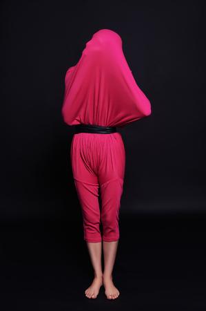 La muchacha oculta la cara entre las ropas inusuales y arte de la moda pose.abstract extraña Foto de archivo - 75262690