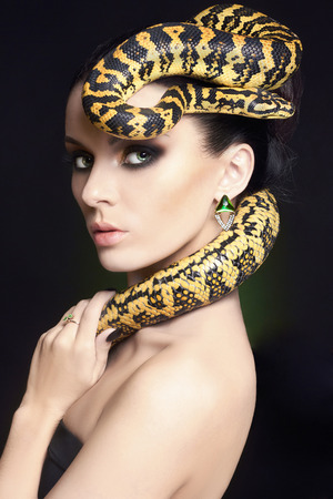 beautiful young woman with Snake on her head like a hair.Brunette model with fashion make up. Beauty close up studio shot.jewelry earrings Фото со стока