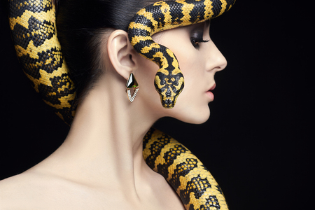 beautiful young woman with Snake on her head like a hair.Brunette model girl with fashion make up. Beauty jewelry earrinrs