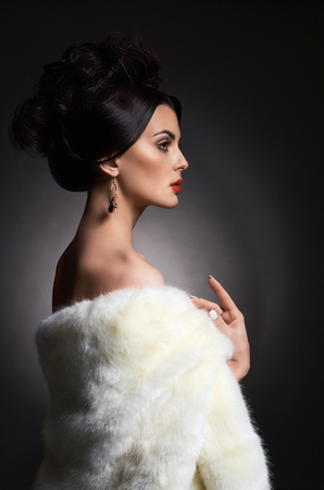 Beautiful woman in fur.fashion Beauty sexy Model Girl with evening hairstyle. Woman in Luxury Fur coat and jewelry
