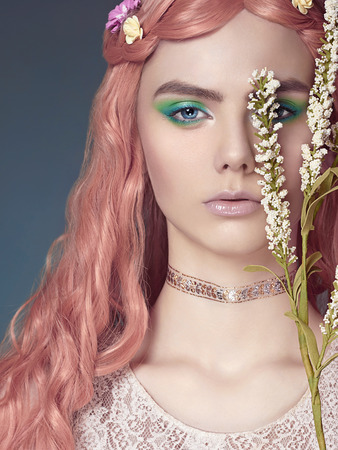 Beautiful girl with pink hair and flowers in them. Fabulous spring portrait of young woman with make up Stock Photo
