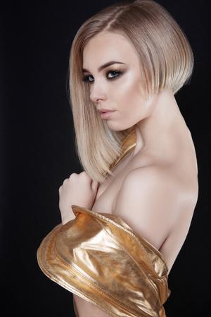 未来的なセクシーな金髪の若い女性黄金ドレス。美しいモデルの女の子が作る