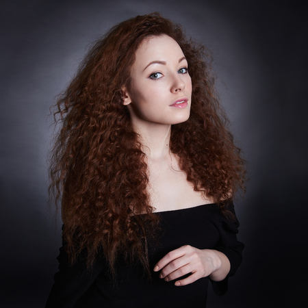 곱슬 머리와 아름 다운 갈색 머리 젊은 여자. 스튜디오 패션 초상화