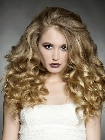 sexy Blonde girl with healthy wavy hair. Beautiful woman with curly hairstyle and make up Stock Photo