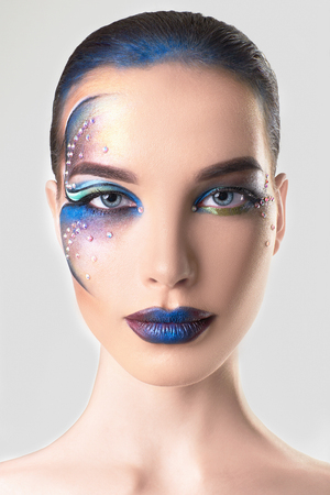 fashion portrait of beautiful young woman with Drawing on her face.colorful make-up beauty girl.blue lips Stock Photo