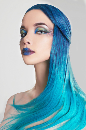 beautiful woman with colorful make-up and blue hair.cristals and drawing on face
