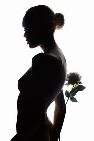 mulher bonita nua com flor rosa. foto de arte moda da silhueta de menina de modelo de corpo perfeito