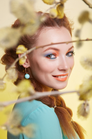 spring happy girl in the branches of a tree. beautiful young woman with colorful make-up Stock Photo