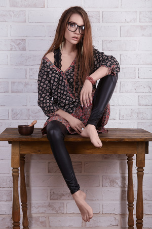 beautiful young woman in glasses. indian style wear hipster girl sitting on retro table over bricks wall