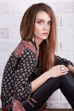 indian style wear hipster girl sitting on retro table over bricks wall.fashion young woman Stock Photo