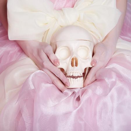 Vrouw in een zijden jurk houdt een schedel.unusuele foto