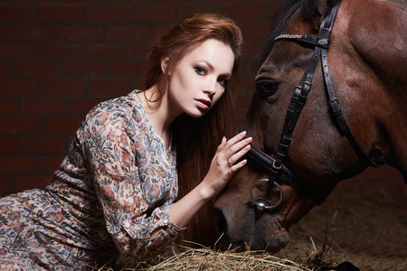 Beautiful young woman with a horse.sensual girl and horse in haysloft