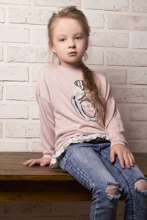 beautiful little Girl in ragged jeans and sneakers.fashion child