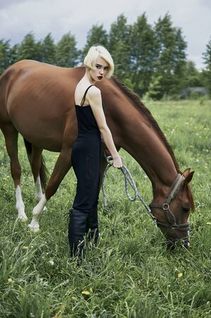 Beautiful blond girl with horse.beauty rider woman and horse Stock Photo