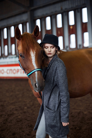 Beautiful girl in hat walking with a horse.beauty young woman and horse
