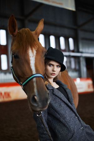 Beautiful girl in hat stay with a horse.beauty young woman and horse Stock fotó