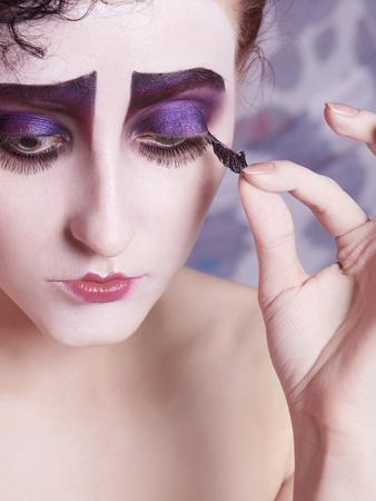 verwijder valse wimpers.vrouw met clown make-up op haar gezicht. Wetenschappelijke beeldschoonheid meisje actrice verwijdert valse wimpers