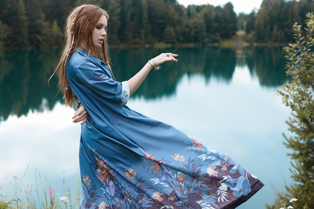 beautiful dancing woman by the lake.walking in forest lifestyle girl dancing in silk dress Stok Fotoğraf