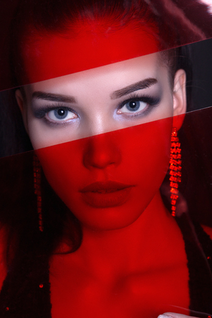 unusual close-up portrait of beautiful girl with make-up and jewelry.female face behind red transparent plastic