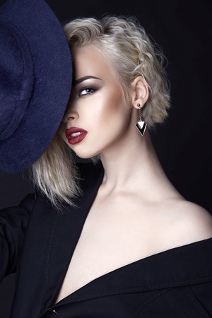 beautiful blond woman with hat.sexy girl with make-up over black background