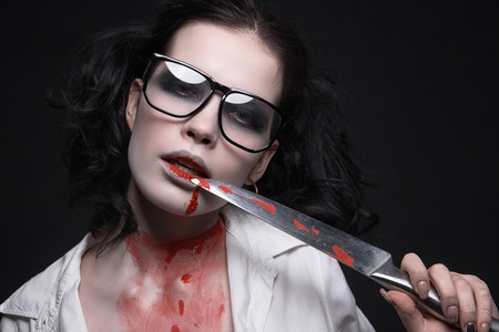 sexy student girl all in the blood with a knife.halloween make-up beautiful woman Stockfoto