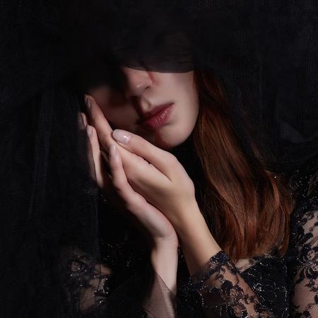 trieste vrouw in zwarte sluier met een bloedige make-up. Halloween-kostuum. zwarte weduwe