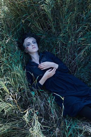 죽은 여자는 잔디에 놓여있다. 할로윈 아이디어입니다. 좀비 소녀 스톡 콘텐츠 - 91867858