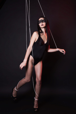 beautiful body puppet woman in under control. doll girl in mask and sexy underwear Stock Photo