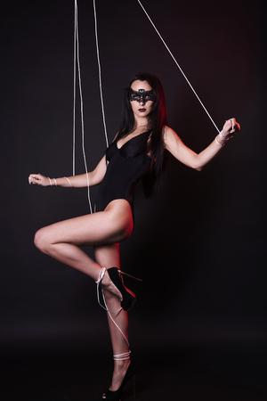 mooi lichaam marionet vrouw in onder controle. poppenmeisje in masker en sexy ondergoed Stockfoto