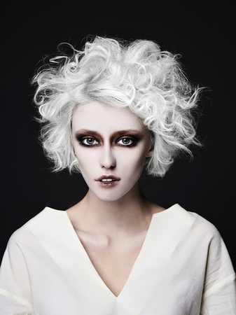 girl with scary clown make-up for halloween.blond young woman with white skin wear straitjacket.psycho person for halloween masquerade
