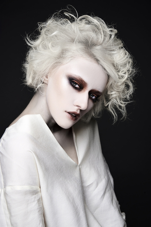 young woman with scary clown make-up for halloween.blonde girl with white skin psycho person for halloweem masquerade Stock Photo